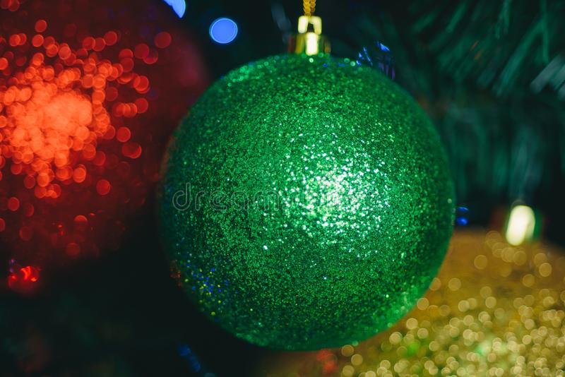 Christmas balls. Background of decorated Christmas tree. New Year Eve mood. Red, green and yellow ball on the Christmas. Tree. Happy New Year stock image