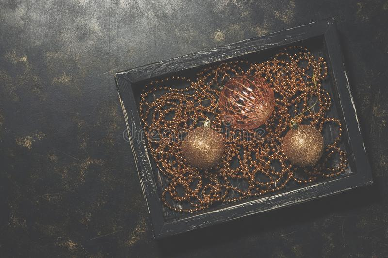 Christmas balls and beads in a black wooden tray on a dark rustic background. Golden Christmas stylish vintage ornaments. Top view royalty free stock images