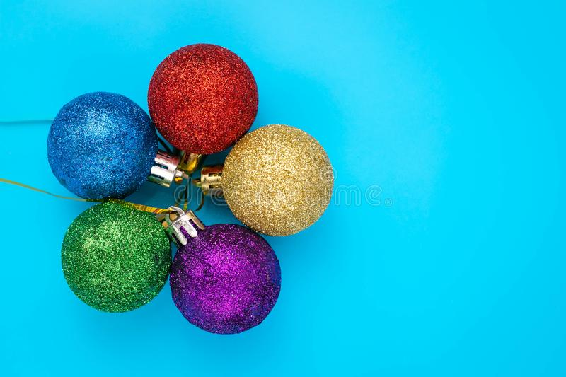 Christmas balls on blue background. New year card with shiny colorful spheres, copy space. royalty free stock photography