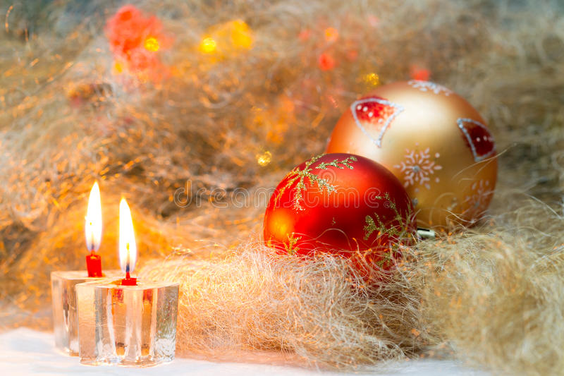 Christmas balls with candles on the background lights. Decorative spider web, in orange, red and yellow colors, two lighted candles in candlesticks icy royalty free stock images
