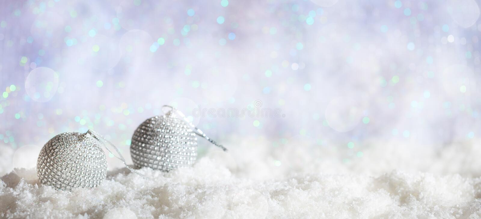 Christmas balls on Christmas snowy bokeh background. Christmas balls on abstract cold winter background with snow and defocused lights stock photography