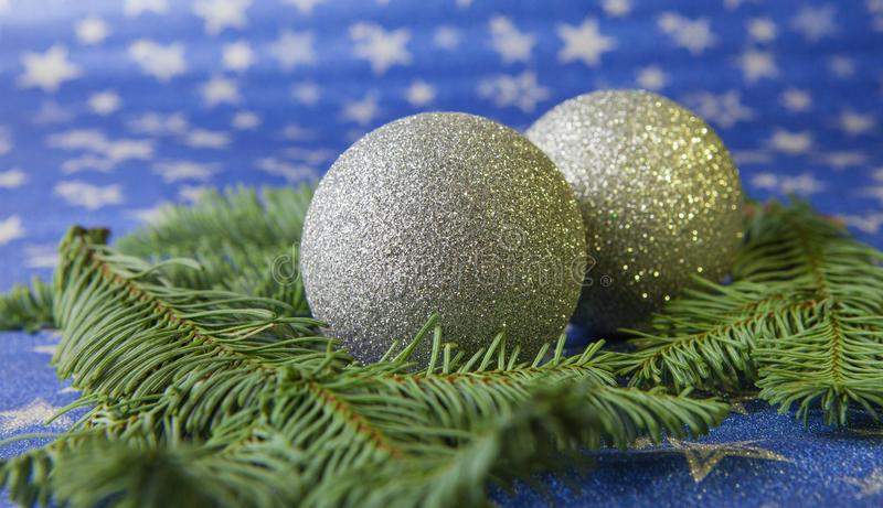 Christmas balls and fir branches on a light star background stock image
