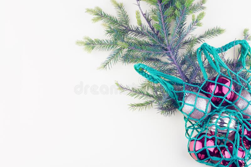 Christmas balls and fir branches in a reusable eco-friendly bag on a light background. royalty free stock photo