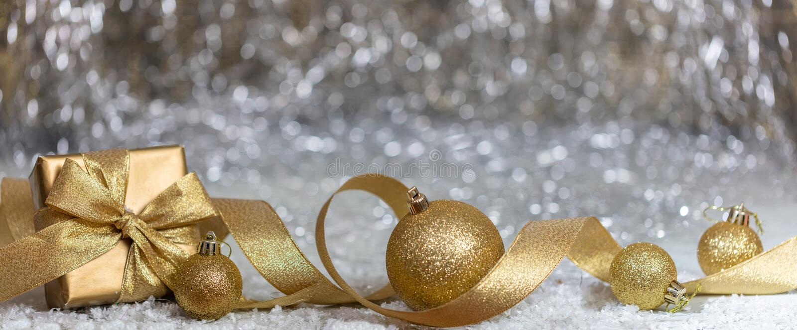 Christmas balls and gift box, golden ribbon and snow, abstract bokeh lights background royalty free stock image