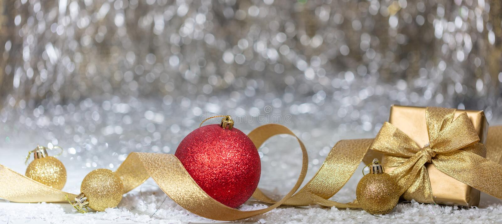 Christmas balls and gift box, golden ribbon and snow, abstract bokeh lights background stock photo