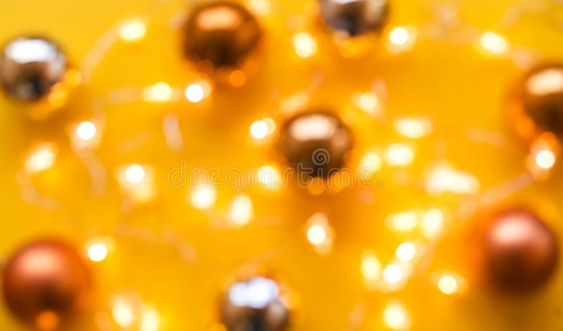 Christmas balls and light bulbs on a yellow background. No focus, blurred royalty free stock photo