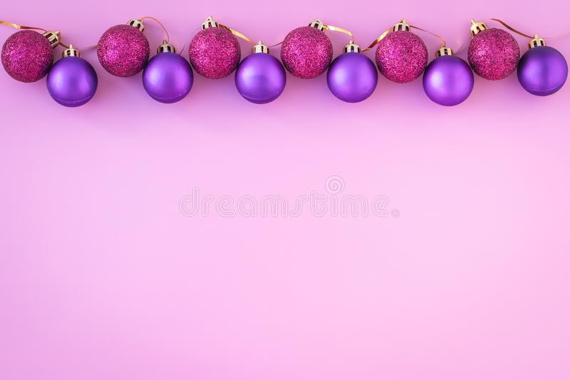 Christmas balls on pink background. Template with copy space. Flat lay, new year mockup. Purple shiny spheres. stock image