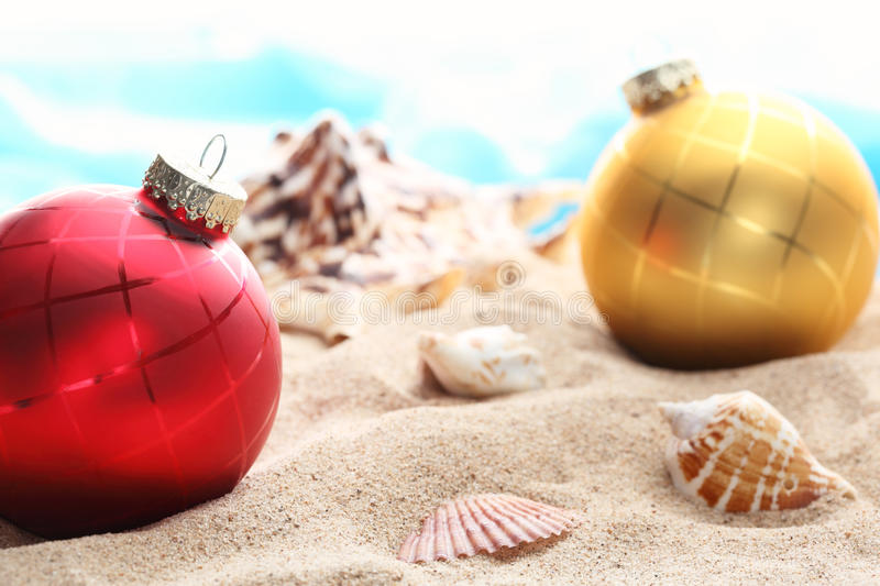 Christmas balls and seashells on the beach royalty free stock images
