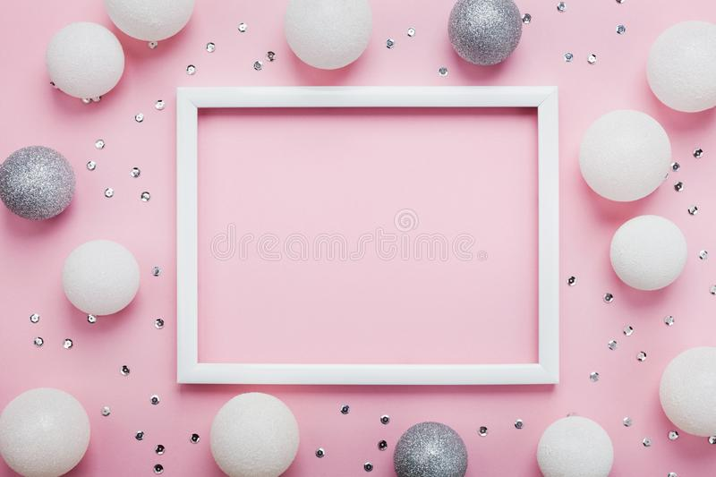 Christmas balls, sequins and picture frame on stylish pink table top view. Fashion background. Flat lay. Party mockup. royalty free stock photography