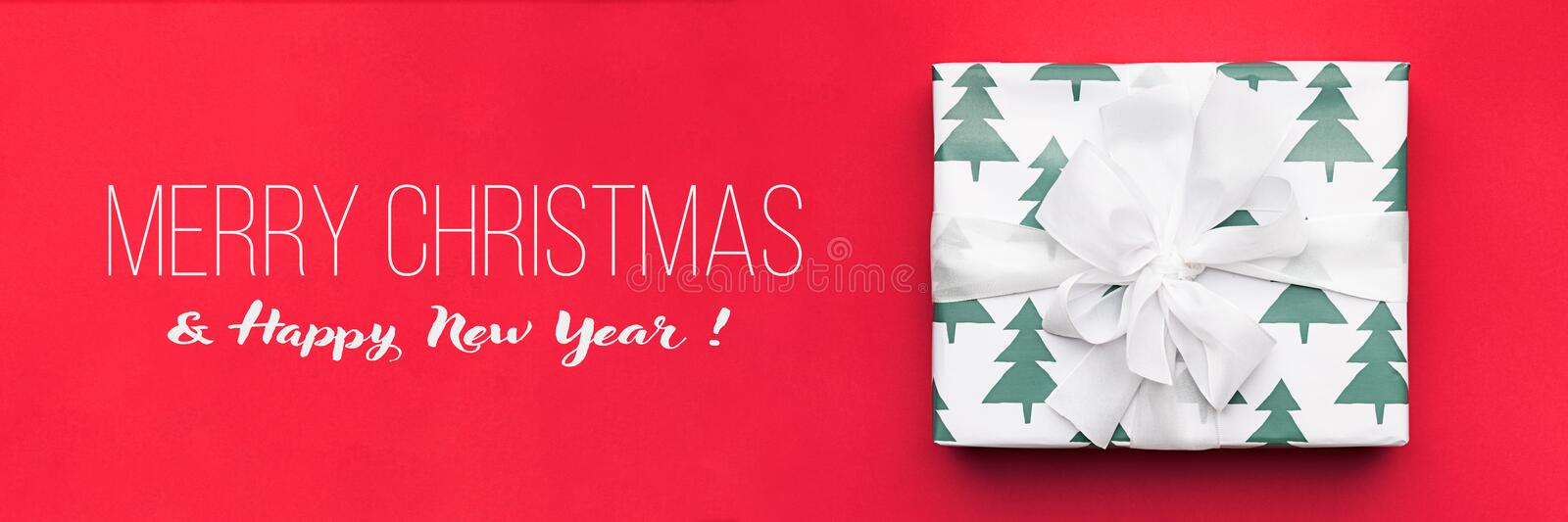 Christmas banner. Beautiful christmas gift isolated on red background. Wrapped xmas box. Gift wrapping. royalty free stock photos