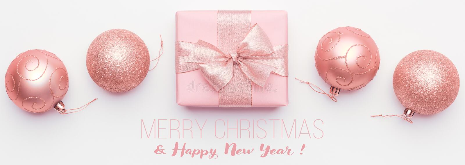 Christmas banner. Beautiful pink christmas gift and ornament baubles isolated on white background. Wrapped xmas box stock image