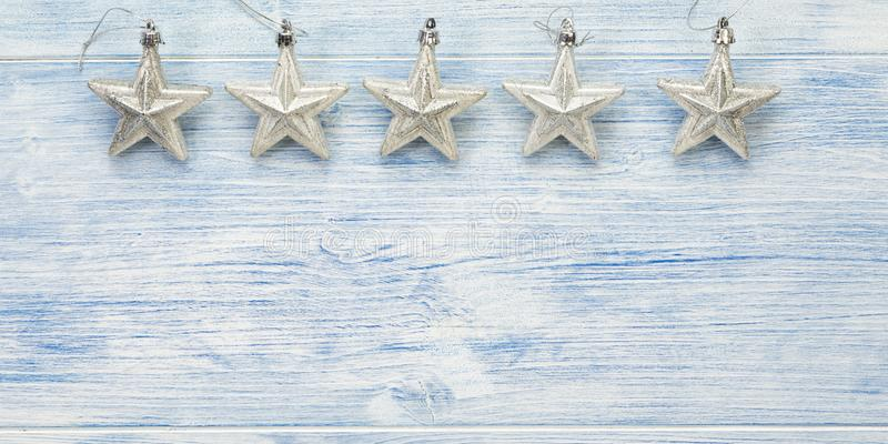 Christmas banner with five silver stars on blue wooden background with copy space royalty free stock photo