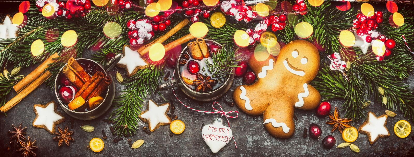 Christmas banner with Gingerbread Man, Cookies, mulled wine ,holiday decorations , fir branches and festive bokeh lighting on dark. Wooden background, top view stock images