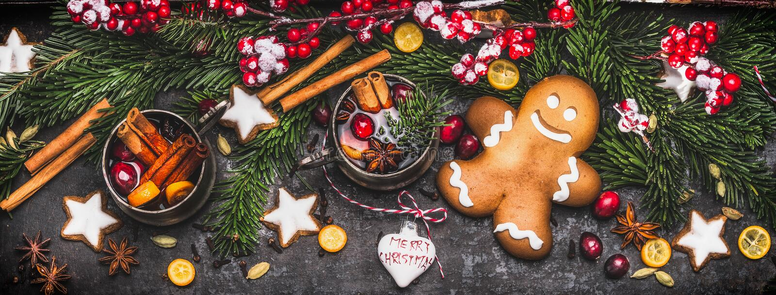 Christmas banner with gingerbread man , mug of mulled wine or punch, fir branches , holiday cookies and festive decoration. And spices, top view royalty free stock photos