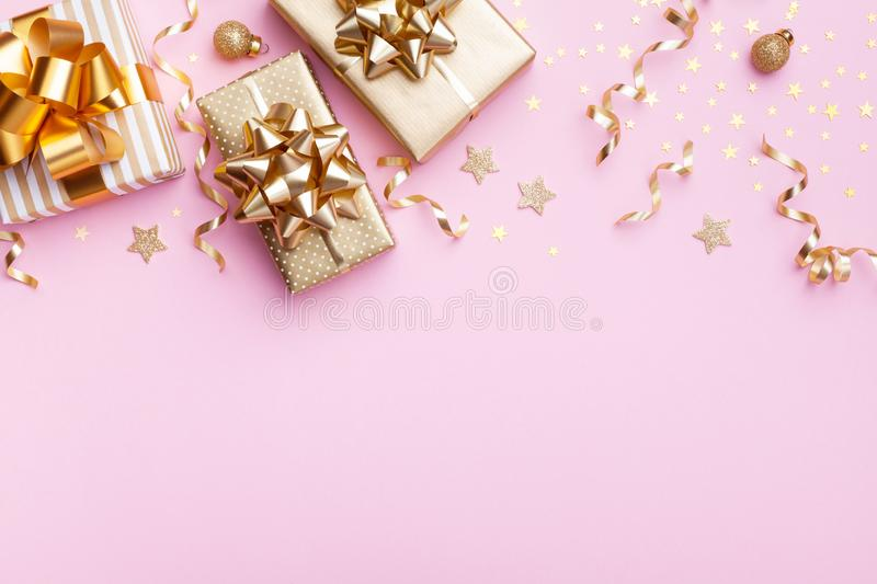Christmas banner. Golden gift or present boxes and star confetti on pink background top view. Flat lay. Card royalty free stock photos