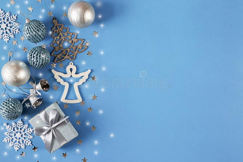 Christmas banner with silver decorations and gift on blue background. Greeting card. Happy New Year. Flat lay. royalty free stock image