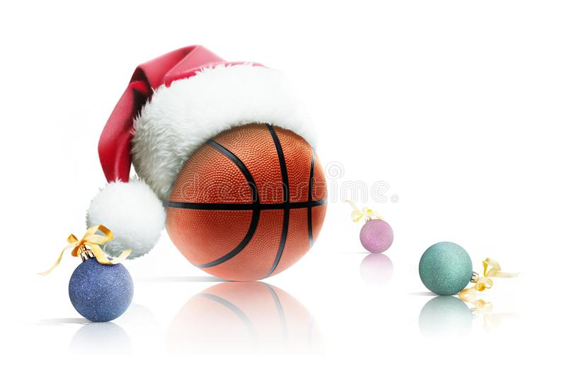 Christmas basketball. Basketball ball in Santa hat Christmas toys on white background. Isolated royalty free stock image