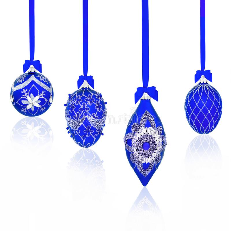 Luxury Blue Jewelled Christmas Bauble Decorations. Luxury blue Christmas tree bauble decorations with bows & ribbons on white background with copy space royalty free stock photo