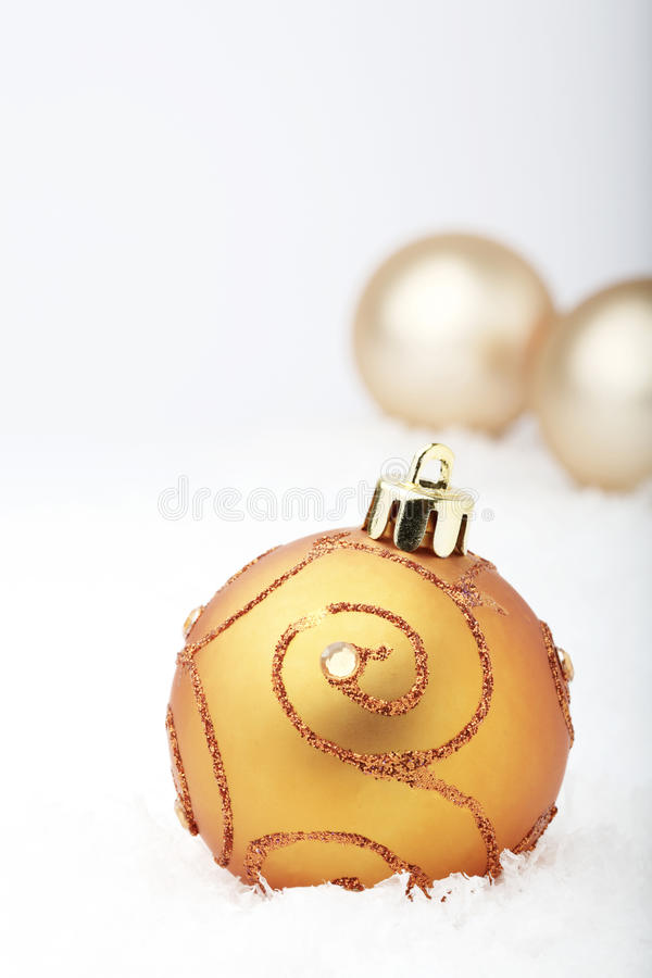 Christmas baubles. A close-up of a gold colored Christmas bauble decoration with a swirl design resting on white snowflakes with two plain baubles in the royalty free stock photo