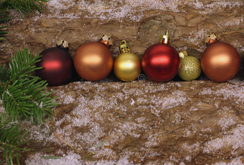 Christmas baubles on firewood logs with snowflakes and fir branches. Row of christmas baubles on firewood logs with snowflakes and fir branches stock image