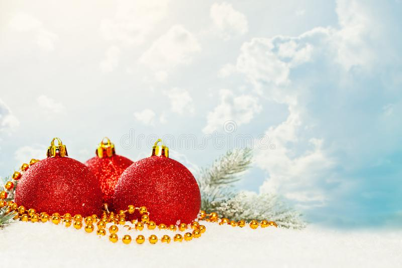 Christmas baubles, gold garland and green fir branch on white snow against blue sky with white clouds. Winter holidays background.  stock images