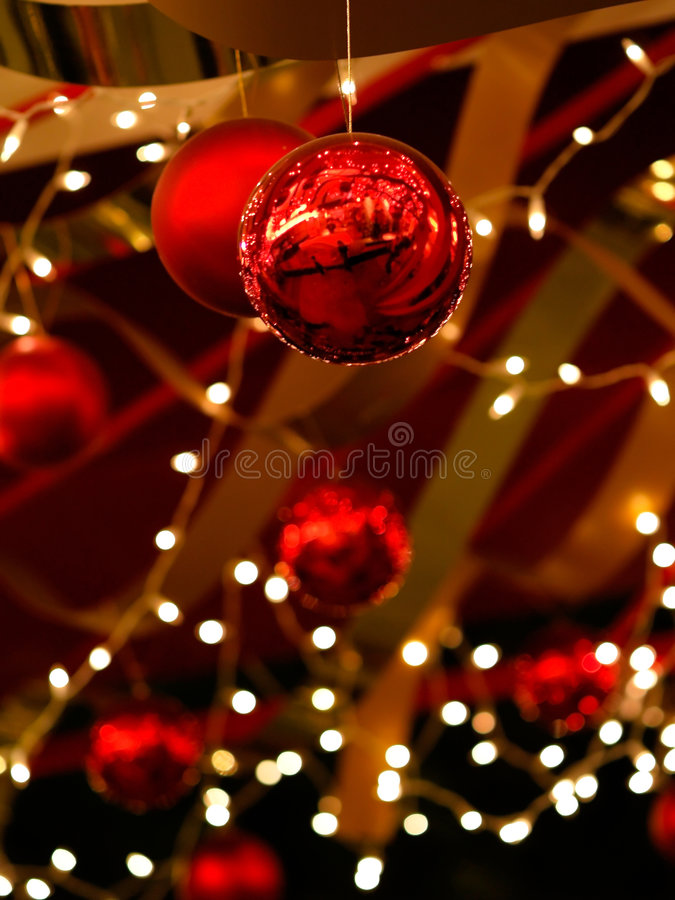 Christmas Baubles and Ribbons. Twinkling lights, baubles and ribbons creating an impression of a richly decorated tree in a Christmas decoration installation in royalty free stock photography