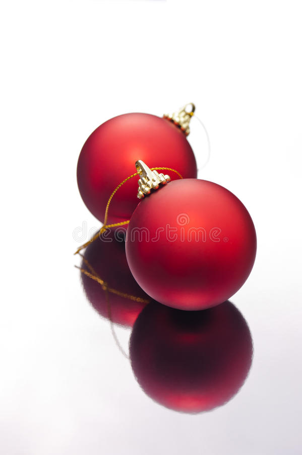 Christmas baubles on a silver reflective surface. Red Christmas baubles on a silver reflective surface royalty free stock photography
