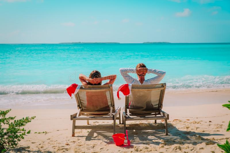 Christmas on beach -chair lounges and happy couple relax at sea stock photos
