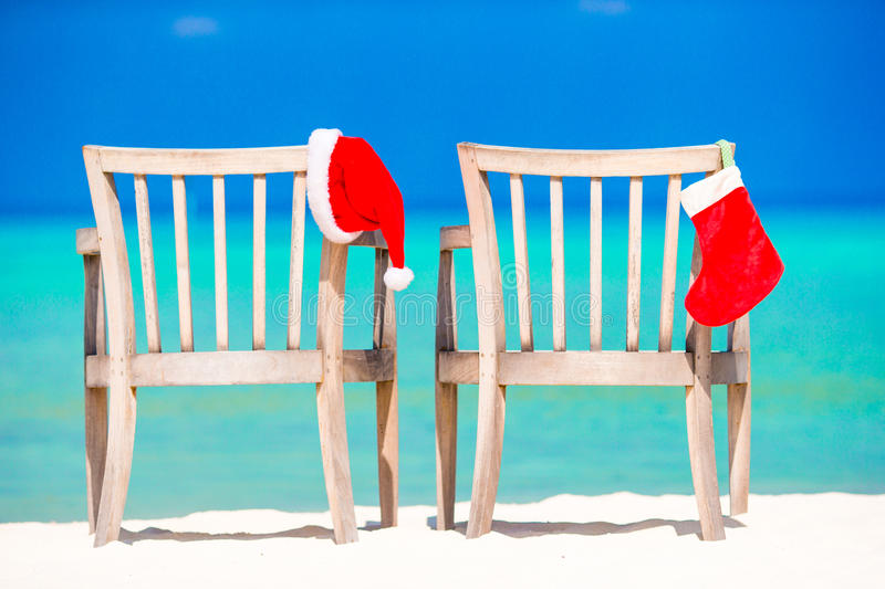 Christmas on beach chairs in cafe with Santa hats at sea. Santa hat on chair longue at tropical caribbean beach royalty free stock photography