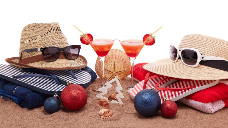 Christmas beach holidays. Beach accessories flip flops, straw hats, seashells, sand, sunglasses, two glasses of cocktail, christmas ornaments on white background stock image