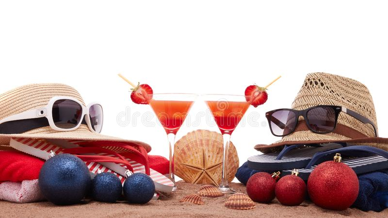 Christmas beach holidays. Beach accessories flip flops, straw hats, seashells, sand, sunglasses, two glasses of cocktail, christmas ornaments on white background stock photos