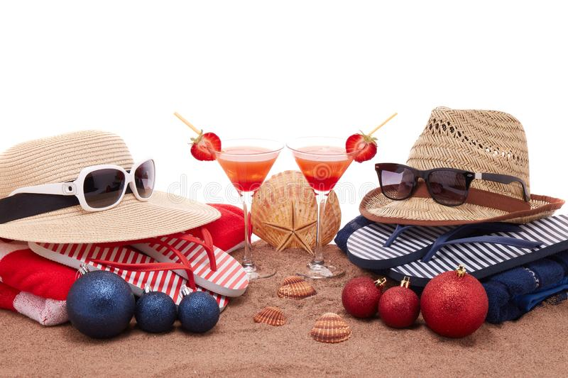 Christmas beach holidays. Beach accessories flip flops, straw hats, seashells, sand, sunglasses, two glasses of cocktail, christmas ornaments on white background royalty free stock photo