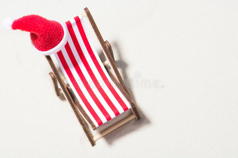 Christmas on the beach: a lounge chair with a Santa hat. Top view royalty free stock photography