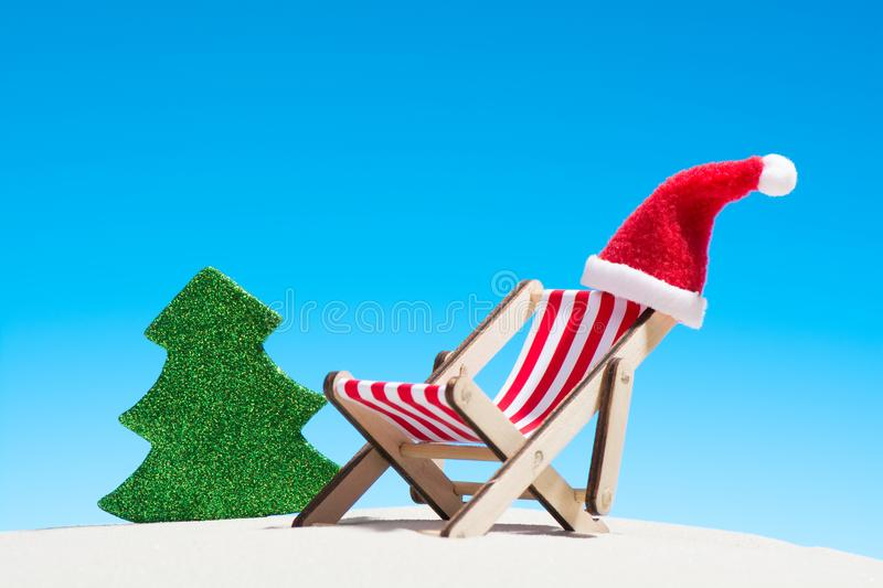 Christmas on the beach: a lounge chair with Santa hat royalty free stock images