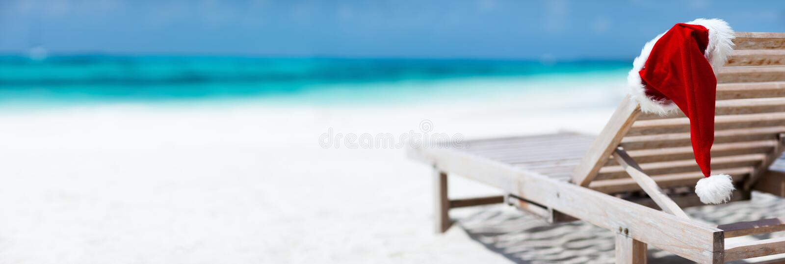 Christmas beach vacation. Panorama of sun chair with Santa hats on beautiful tropical beach with white sand and turquoise water, perfect Christmas vacation royalty free stock photo
