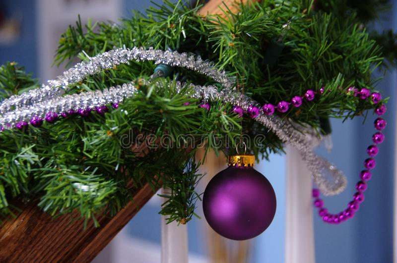 Christmas beads balls ornaments. A green wreath with Christmas beads and balls adorn a hand rail signifying the joy of the season stock photography