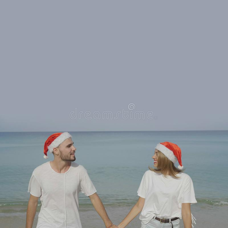 Couple Wearing Santa Hat At The Beach Stock Photo