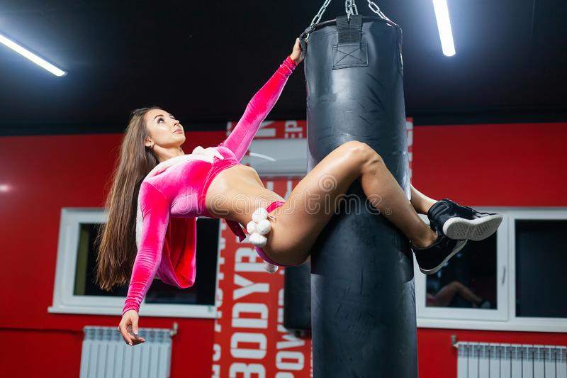 Christmas. A beautiful muscular woman in a Santa Claus costume hangs from a Boxing bag. GYM. Christmas. A beautiful muscular woman in a Santa Claus costume stock images