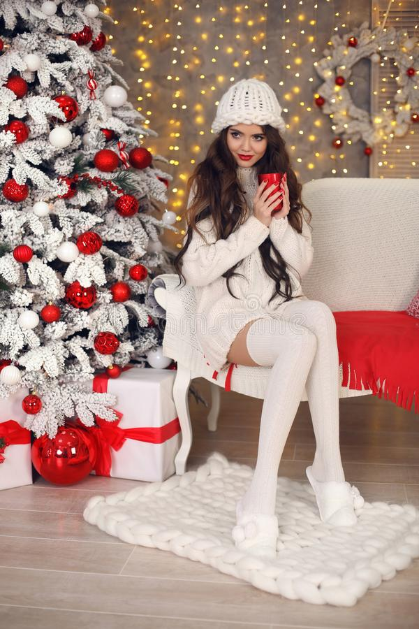 Christmas. Beautiful pretty woman in white knitwear sweater, handmade hat and cozy socks relax on knitted blanket. Healthy long stock image