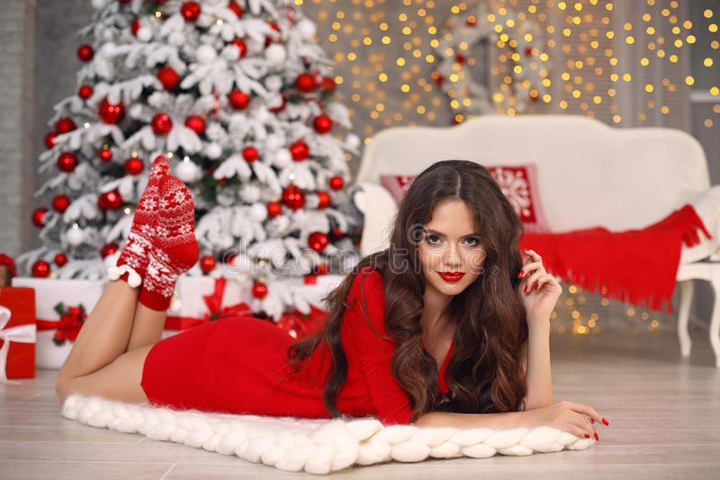 Christmas. Beautiful santa girl. Smiling woman with long hair and red lips makeup lying on white knitted chunky yarn blanket in royalty free stock image