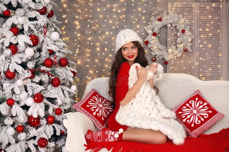 Christmas. Beautiful santa girl. Smiling woman with long hair sitting on cozy sofa holding white knitted chunky yarn blanket in royalty free stock image
