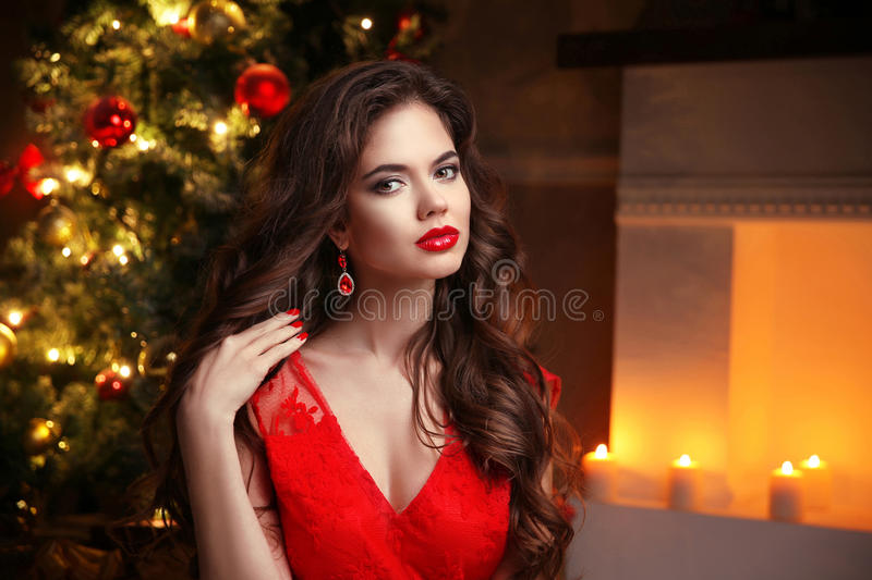 Christmas. Beautiful smiling woman. Fashion ruby earrings jewelry. Makeup. Healthy long hair style. Elegant lady in red dress. Over christmas tree lights stock image