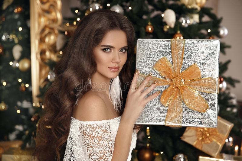 Christmas. Beautiful smiling woman with gift box. fashion interior photo of gorgeous brunette. Makeup. Healthy long hair style. E. Legant lady in white dress royalty free stock image
