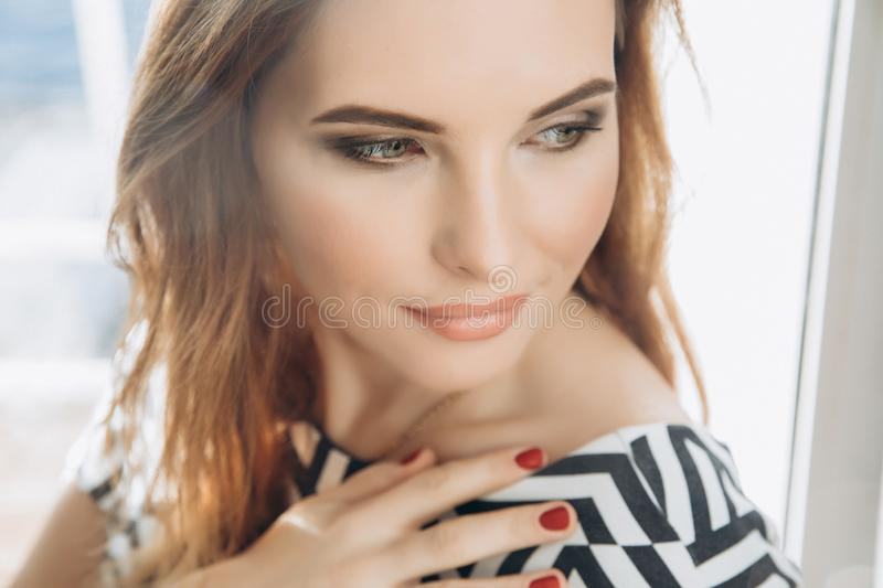 Beautiful smiling woman. Manicure nails. Makeup. Red long hair style. Elegant lady in black and white dress. Christmas. Beautiful smiling woman. Manicure nails royalty free stock images