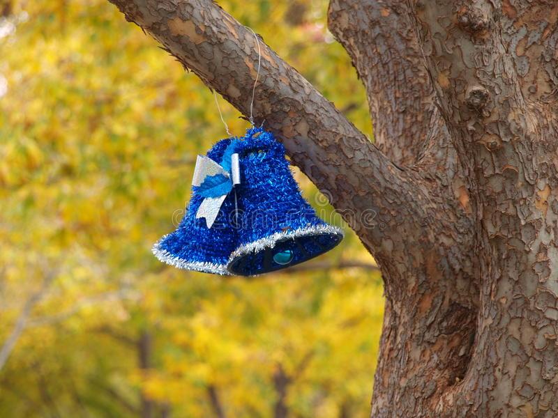 Christmas Bells. A pair of blue and silver tinsel bells with ornament clappers hang from a tree branch in a park stock image