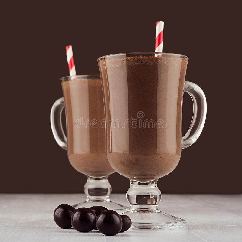 Christmas beverage - hot chocolate in mug with round chocolate candies and red striped straw in elegant dark brown interior. Christmas beverage - hot chocolate royalty free stock photography