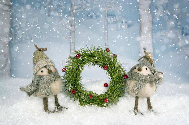 Christmas Birds Wreath. A pair of whimsical birds dressed in hats and scarves holding a Christmas wreath. birch trees and village in background royalty free stock image
