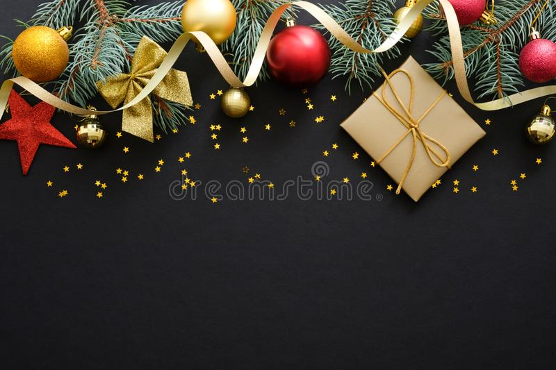 Christmas black background with fir tree branches, decorations, red and golden baubles. gift box, confetti. Christmas, winter. Holiday, New Year concept. Flat royalty free stock image