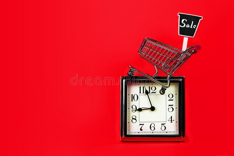 Christmas Black Friday Sale concept with silver clock, shopping cart shop trolley with sign sale on red background. stock photography
