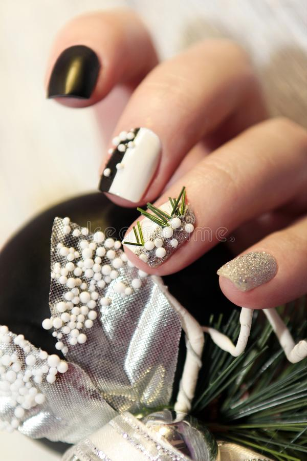 Christmas black and white manicure. With silver balls and Christmas ornament on female hand close up royalty free stock photography
